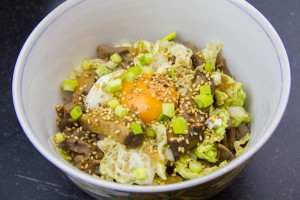 Versez un jaune d'œuf et saupoudrez de graines de sésame et cébette.