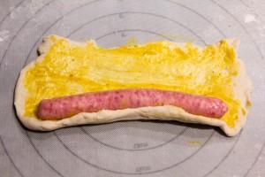 Placez la saucisse à l'extrémité du rectangle et roulez la dans la pâte à pizza