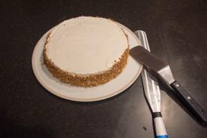 Déplacez le gâteau sur son plat de service après avoir déposer sur son pourtour des brisures de fruits secs ( noisettes) ou de spéculos