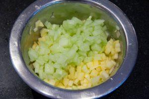 Versez les désde pommes dans le bol contenant les dés de concombre et mélangez avec le jus d'un demi citron vert
