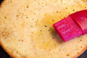 Déposez une tranche de sponge cake au fond du cercle et imbibez le de sirop à l'aide d'un pinceau