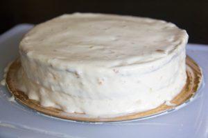 Sortez le gâteau et démoulez le. Recouvrez alors tout le pourtour du gâteau de crème à l'aide d'une spatule
