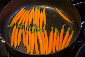 Faites revenir les carottes juste quelques minutes dans une poêle avec une grosse noix de beurre, le zeste de l'orange et une cuillerée à soupe de jus d'orange