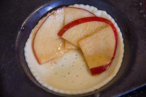Disposez les tranches de pommes dans les tartelettes en faisant se chevaucher les deux moitiés de pommes
