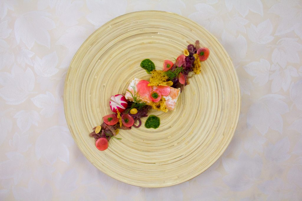 Saumon confit à l'huile basse température, compoté d'oignon rouge et fenouil, radis croquants et pistou coriandre