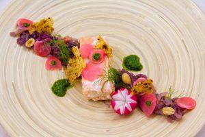 Saumon confit à l'huile basse température, compoté d'oignon rouge et fenouil, radis croquants et pistou coriandre noisette