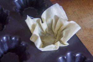 Pliez les feuilles en deux ou en quatre selon leur grandeur et disposez-les dans des moules en silicone ou en inox bien beurrés