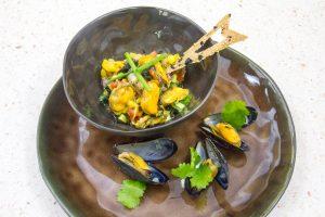 Disposez une petite louche de salade dans des bols individuels. Puis décorez avec quelques brins de ciboulette, des moules en coquilles, quelques feuilles de coriandre