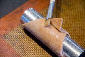 Et on enroule les carrés de pâte sur les rouleaux. Puis badigeonnez le dessous de la pointe