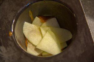 Disposez aussitôt des petites lamelles de pomme dans le fond des moules pour faire une rosace
