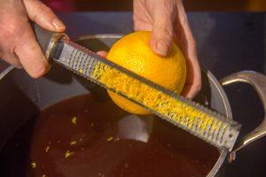 Zestez les oranges au dessus de la casserole contenant le vin rouge