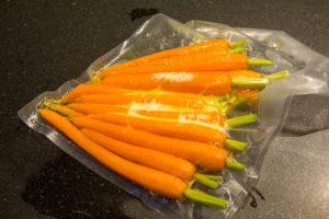 Mettez les carottes fanes sous vide avec le zeste de l'orange et une noix de beurre