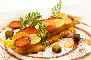 Finissez avec les chips de fanes de carottes, les dés de pain d'épices et quelques rondelles de carottes tout autour