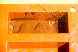 Versez une petite cuillère de chocolat fondu dans le fond des moules