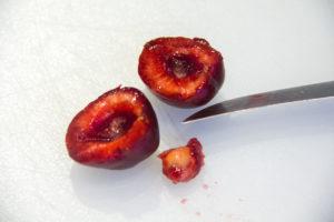 Equeutez les cerises et coupez-les en deux