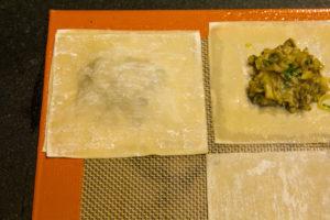 Recouvrez chaque raviole farcie d'un autre carré de raviole et soudez bien les bords avec vos doigts en essayant d'emprisonner le moins d'air possible.