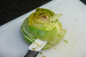 Puis à l'aide d'un couteau tournez autour de l'artichaut pour en enlever progressivement les feuilles jusqu'au cœur