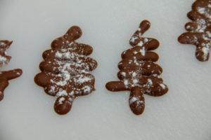 Saupoudrez les sapins en chocolat avec du sucre glace